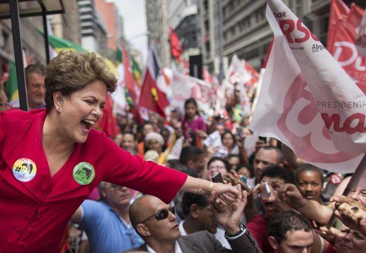 Dilma Rousseff, quien va por la reelección, saluda a sus partidarios en un mitin de campaña en Porto Alegre, Brasil. (Agencias)