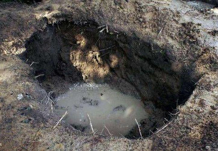 En la fosa fueron exhumados 31 cuerpos. (Milenio/AFP)