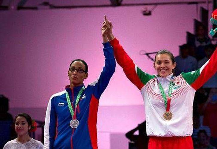La delegación cubana asegura que la campeona mundial Glenhis Hernández (i) estaba lesionada en una mano y por eso tuvo que levantarla de la manera que lo hizo en la premiación, al lado de la mexicana María Espinoza. (mexsport.com)