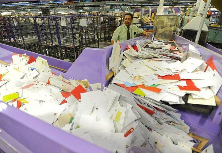 En la imagen, un empleado del servicio postal supervisa el proceso de envío de correspondencia. (Archivo/EFE)