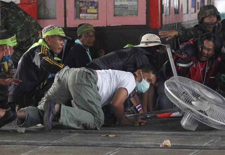 Un opositor del gobierno se resguarda después de disparar su arma durante una manifestación de partidarios de la administración en Tailandia. (Agencias)