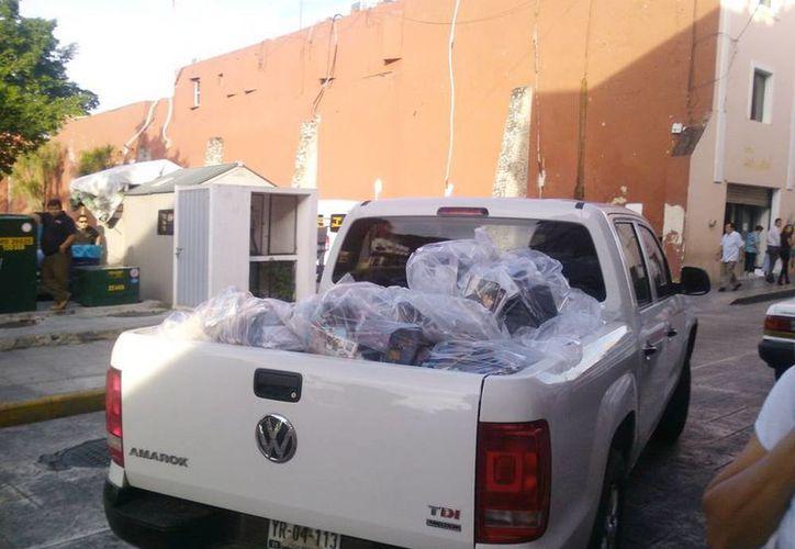 Imagen del traslado del material apócrifo decomisado ayer en una tienda enfrente del estacionamiento del Ayuntamiento de Mérida. (Milenio Novedades)