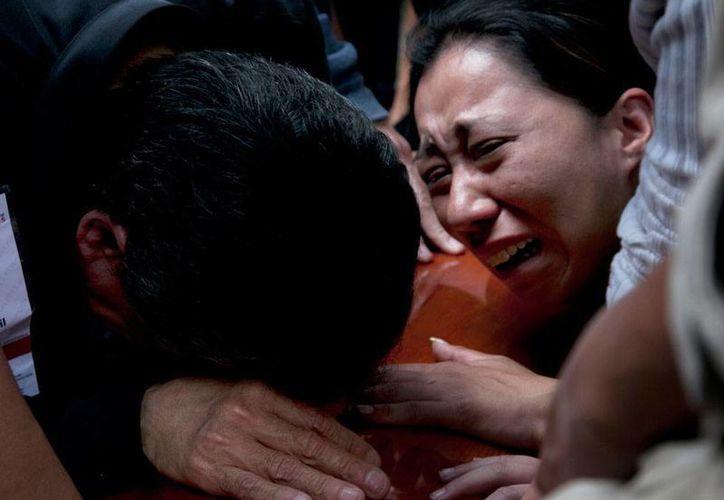 Según la Pgjdf, al periodista mexicano -cuyos familiares aparecen en la imagen, durante su velorio- Rubén Espinosa Becerril y sus acompañantes, los mataron tres personas, una de las cuales ya está detenida. (AP/archivo)