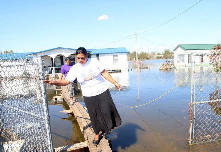 Vecinas del complejo de casas móviles 'Los Arrancones', utilizan un puente casero de madera para ingresar a una de las casas, a casi dos semanas después del paso del huracán Matthew por Carolina del Norte. (EFE)