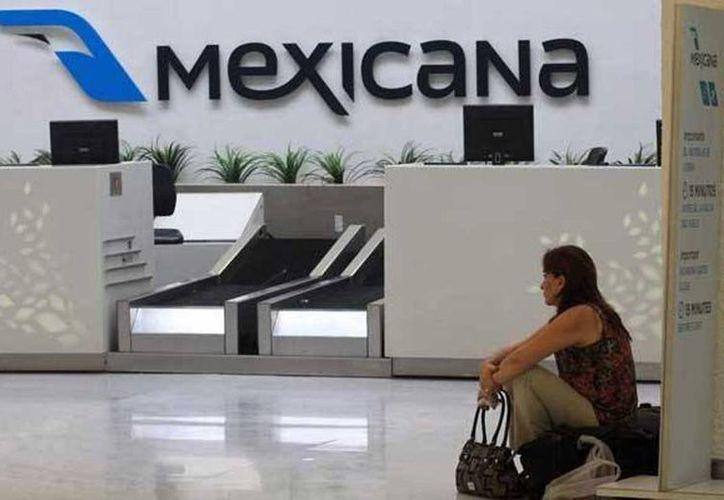 La sindicatura mexicana anunció la puja para vender los bienes inmuebles de la extinta aerolínea. Imagen de un mostrador de Mexicana de Aviación en el AICM. (Archivo/Notimex)