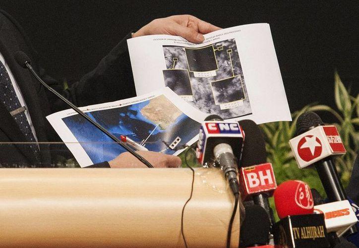 El ministro de Defensa malasio, Hishamuddin Hussein, muestra nuevas imágenes de lo que podrían ser los restos del avión de Malaysia Airlines. (EFE)