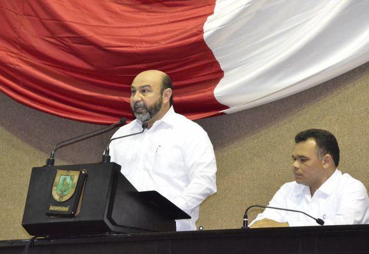 El diputado Luis Hevia durante su discurso. Lo acompaña el gobernador Rolando Zapata. (SIPSE)