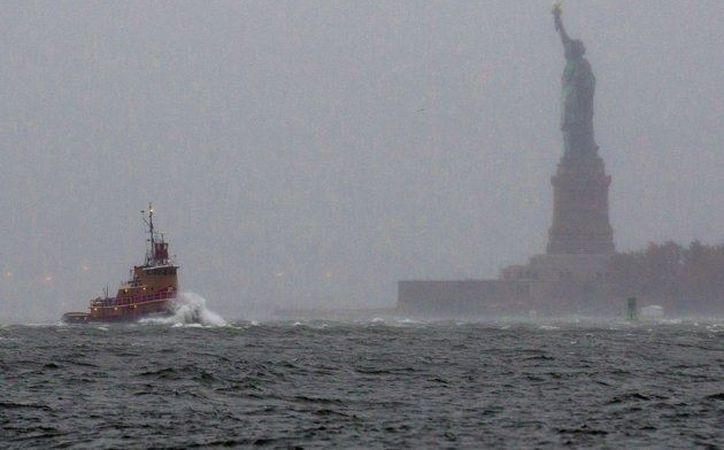 Las olas impactan la proa de un bote que pasa cerca de la Estatua de la Libertad, en Nueva York. (Archivo/AP)