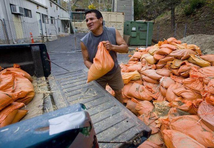 Eddie Armas, residente de Silverado Canyon, transporta costales de arena en su camioneta en espera de las fuertes lluvias que se pronostican. (Foto: AP)