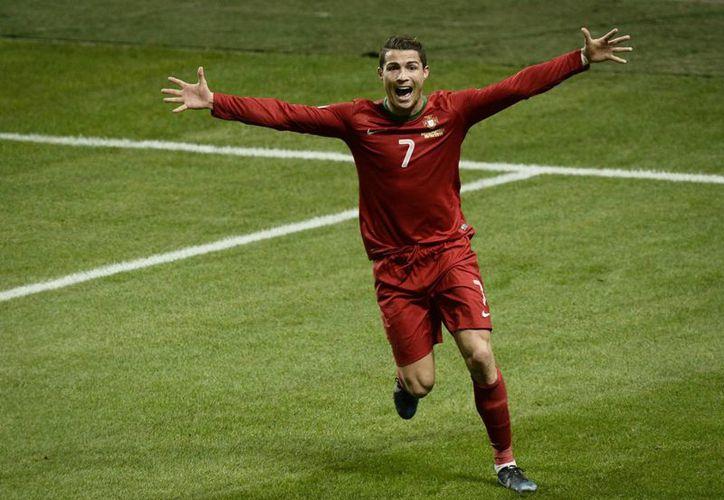 Cristiano Ronaldo celebra uno de los tres goles que le anotó a Suecia para que Portugal lograra la clasificación al Mundial 2014, en el repechaje europeo. (Agencias)