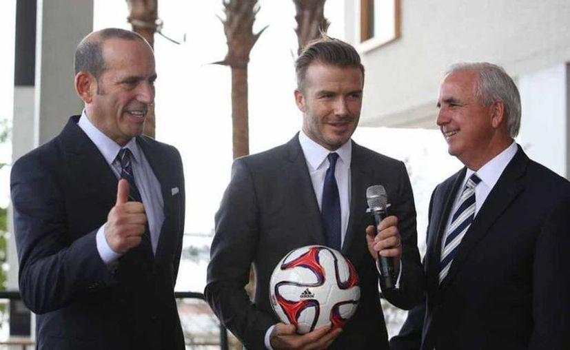 El exfutbolista y empresario David Beckham visitó a una familia mexicana y les regaló Ipods y un cheque millonario, en el marco de la grabación de un programa de tv. En la foto, con directivos con los que se ha puesto de acuerdo para la construcción de un estadio. (miamiherald.com)