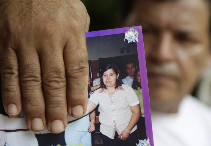 José Amarilla sostiene una fotografía en la que aparece su hija Rosalía Amarilla, en Nemby, Paraguay. (Agencias)