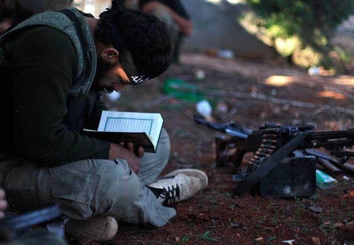 Bombardeos contra bastiones sirios tomados por el Estado Islámico dejaron este martes más de 50 muertos. La imagen no corresponde al hecho; está utilizada solo con fines ilustrativos: un rebelde en Siria lee el Corán. (AP/Archivo)