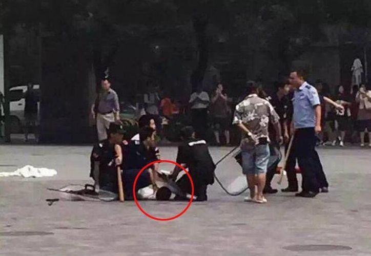 Momento en que los agentes detienen al hombre que atacó a una mujer y a su acompañante en China. (twitter.com/sanverde)