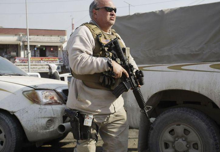 Un hombre armado se observa en guardia cerca del cuartel de Policía de Kabul, Afganistán, donde un asesor de EU fue muerto. (Agencias