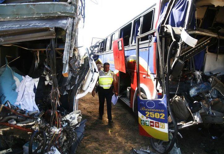 Un policía camina en medio de dos autobuses accidentados en una autopista en el oeste de Venezuela. (EFE)