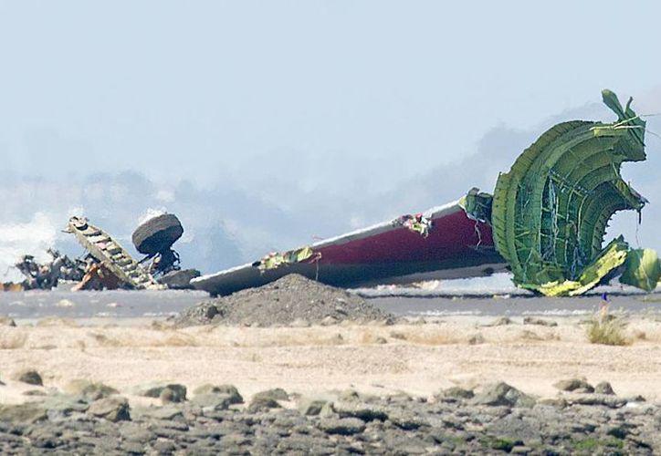 Esta es la cola y otras partes del avión que se desprendieron al chocar contra la pista de aterrizaje. (Agencias)