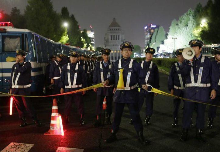 La policía hace guardia ante el Parlamento nipón en Tokio ante las protestas que se realizan en la ciudad. (EFE)