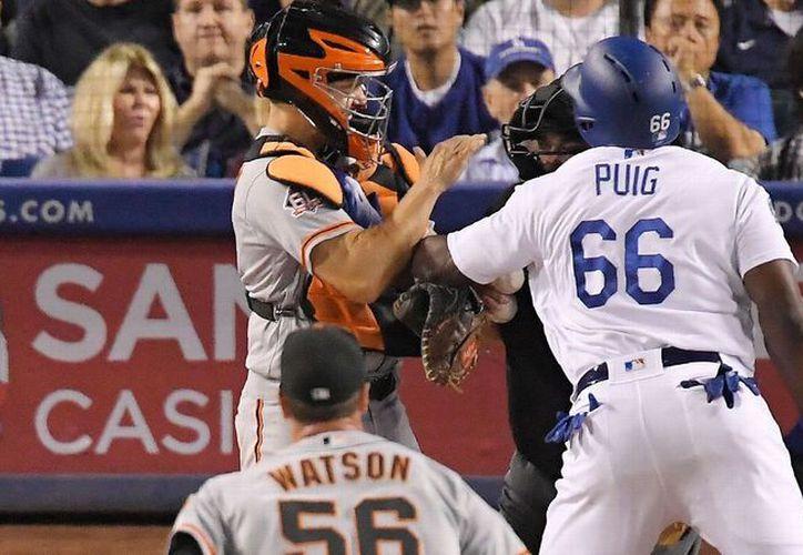 Los beisbolistas de los Dodgers de los Ángeles, Yasiel Puig y de Gigantes de San Francisco, Nick Hundley discutieron y se agarraron a golpes en la séptima entrada del partido. (Foto:abc7news.com)
