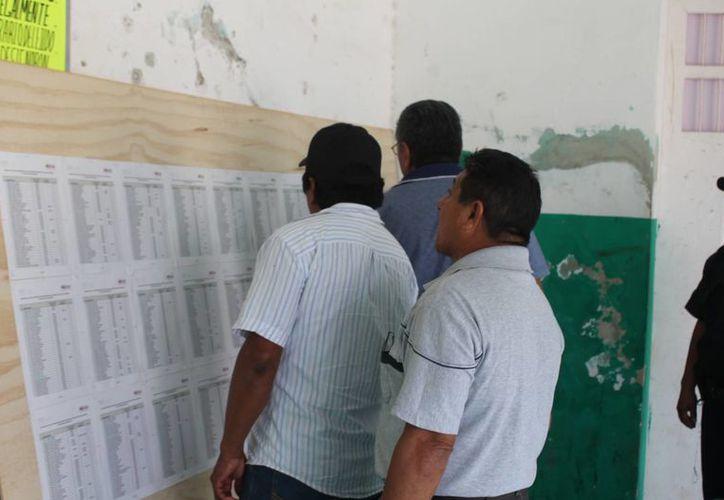 En los pasillos está la lista de ejidatarios beneficiados con títulos y certificados. (Raúl Balam/SIPSE)