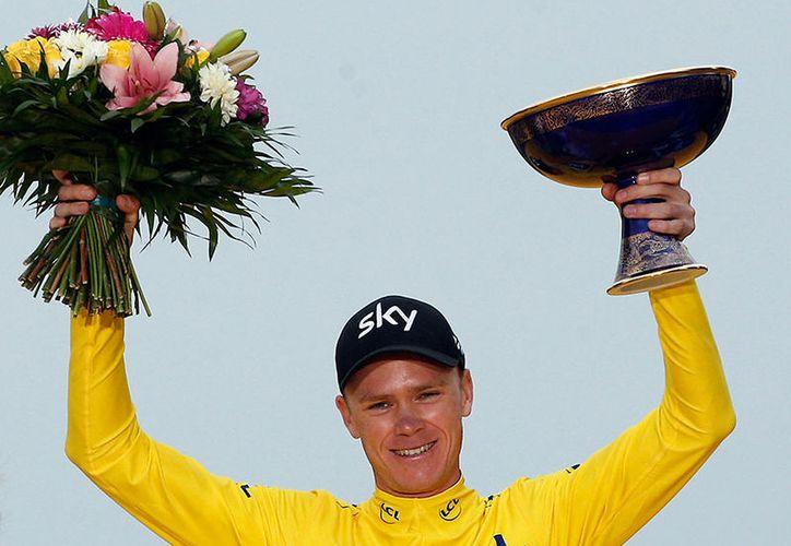 Froome lució emocionado y con ojos llorosos al alzar el ramo de flores para el ganador.  (AP)
