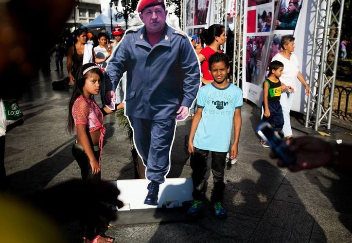 Niños portan una imagen de tamaño casi natural del fallecido presidente venezolano Hugo Chávez, durante la conmemoración del Día Internacional de la Mujer en Caracas, el sábado 8 de marzo. (Agencias)