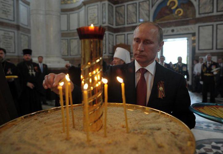 Putin enciende una vela en la catedral de San Vladimir en Sebastopol donde asistió a las celebraciones del Día de la Victoria. (Agencias)