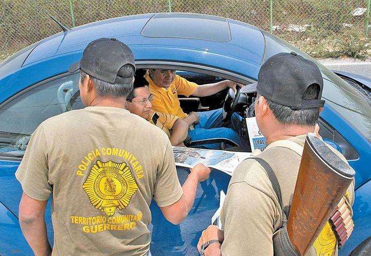 Policías comunitarios de la montaña revisan un vehículo. (Milenio)