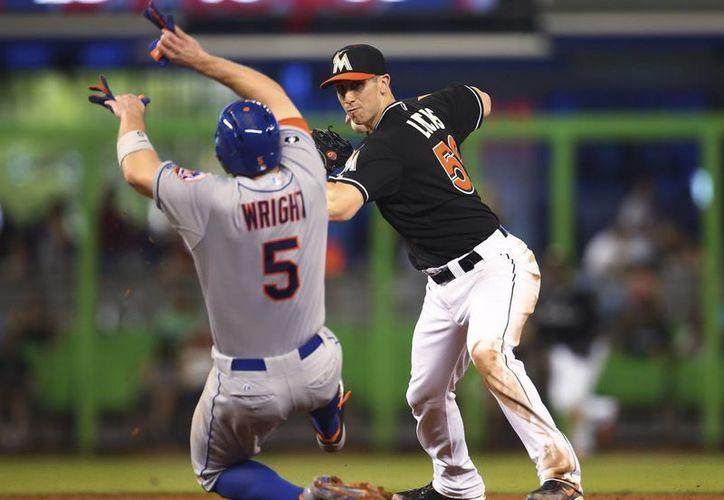 Tras dejar fuera a David Wright (5), de Mets, en segunda, el marlín Ed Lucas (59) hace un lanzamiento para completar un doble play. (Foto: AP)