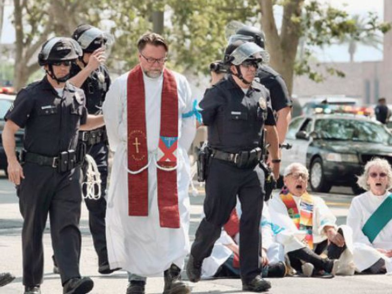 A clergy member is arrested during a civil disobedience protest in front of Federal Courthouse in Los Angeles. (AP)