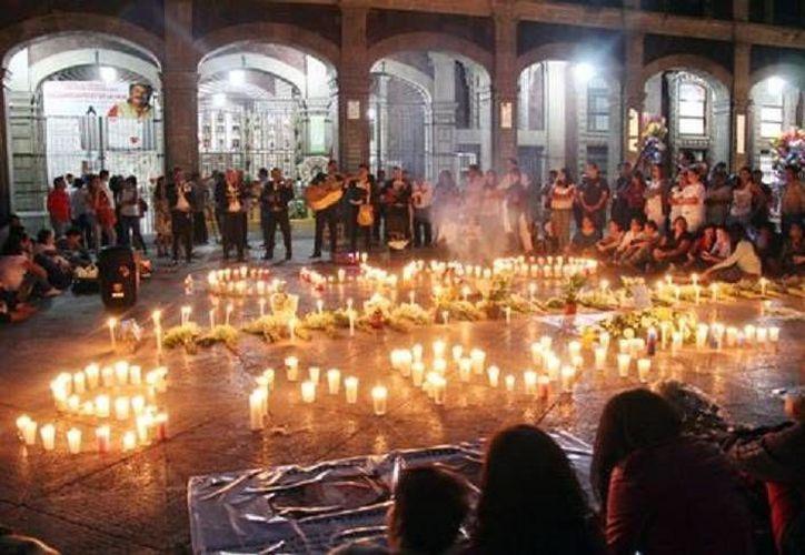 """Este martes, estudiantes de la UAEM recordaron, con danzas prehispánicas, lecturas y velas que formaban las palabras """"Chao"""" y """"Sara"""", al doctor Alejandro Chao Barona y a su esposa. (Cuartoscuro)"""