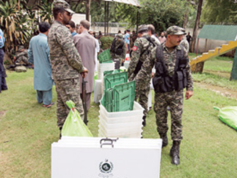 Pakistani soldiers guard a polling material assigned to staff at a distribution center in Islamabad, Pakistan.