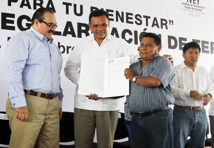El gobernador Rolando Zapata (c) entrega su título de propiedad a uno de los beneficiarios. (SIPSE)