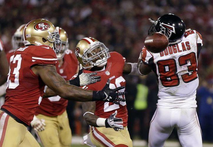Navorro Bowman (53) intercepta un pase dirigido al halcón Harry Douglas (83), antes de una carrera de touchdown de 89 yardas en la segunda mitad del encuentro entre los 49ers y los Halcones de Atlanta. (Agencias)