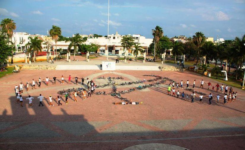 Cerca de 70 personas participaron para darle forma una bicicleta humana en Playa del Carmen. (Daniel Pacheco/SIPSE)