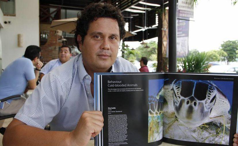 Luis Javier Sandoval con su fotografía ganadora. (Tomás Ávarez/SIPSE)