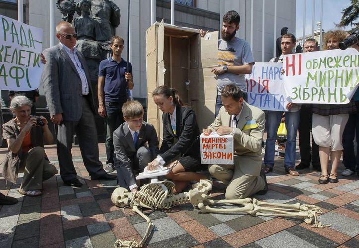 Varias personas muestran un esqueleto que simboliza la ley que trata de restringir las manifestaciones, en frente de la sede del Parlamento en Kiev, Ucrania, en el marco de las protestas contra su presidente. (EFE/Archivo)