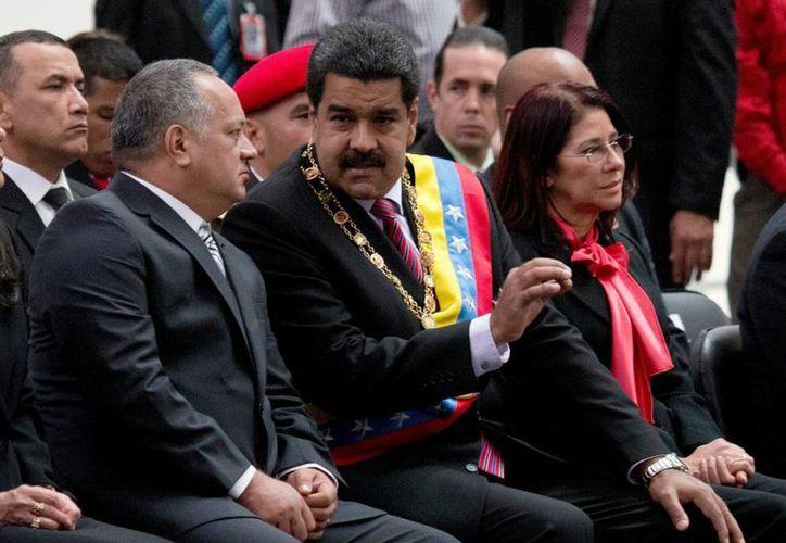 Imagen del presidente de Venezuela, Nicolás Maduro (centro) mientras habla con el ahora ex presidente de la Asamblea Nacional, Diosdado Cabello (izquierda). Maduro modificó la semana pasada parte de su equipo ministerial e incorporó algunas nuevas caras a su gabinete económico. (AP Photo / Fernando Llano, Archivo)