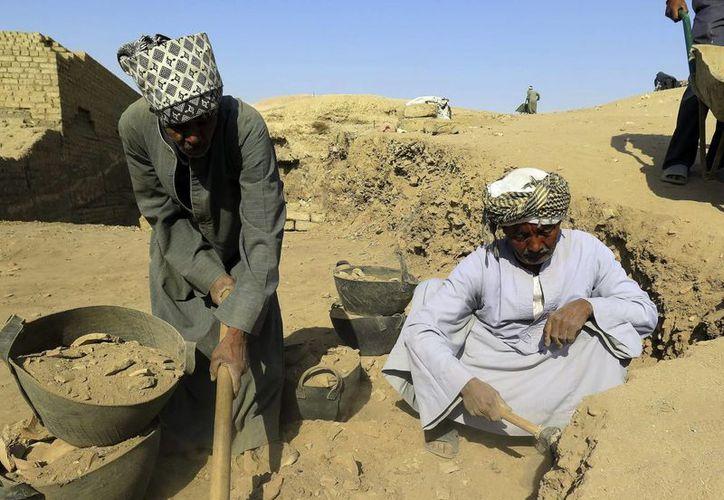 Mohamed al Arian (d), que forma parte del equipo del Proyecto del Templo de Tutmosis III, trabaja desde los 11 años en misiones de este tipo. (EFE)