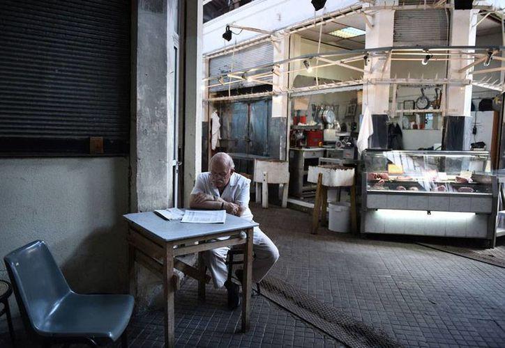 Grecia alcanzó un acuerdo para solucionar la crisis de pagos de su deuda. La imagen, utilizada solo con fines ilustrativos, muestra a una persona mientras lee un periódico, en un sitio comercial que luce abandonado. (AP)