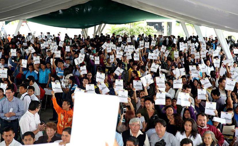 Estudiantes muestran en el aire las becas que recibieron ayer de manos del Gobernador, durante la entrega de esta ayuda a alumnos del ITM y UTM en Mérida. (Milenio Novedades)