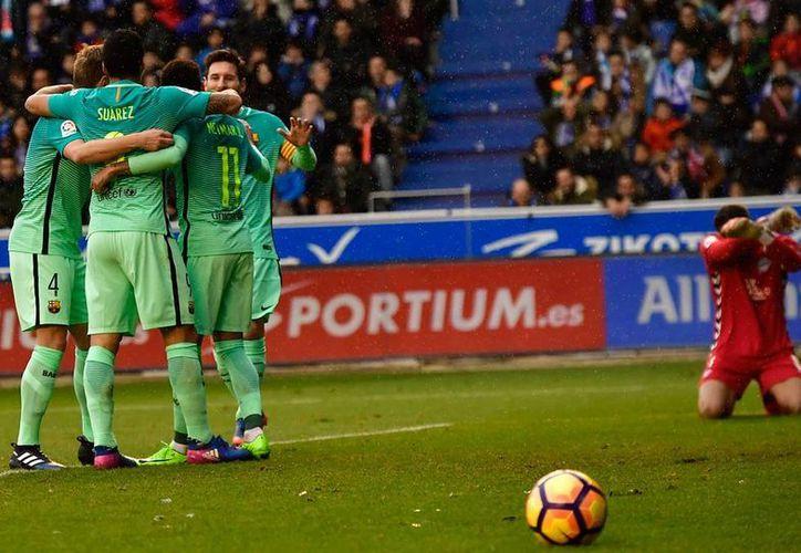 Jugadores del Barza se abrazan para festejar uno de los seis goles que le metieron ayer a la endeble defensa del Alavés, en la Liga de España. (AP)