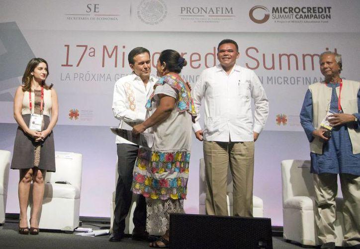 Aspecto de la inauguración de la 17 Cumbre Mundial del Microcrédito en Mérida, con la presencia del gobernador de Yucatán, Rolando Zapata Bello; el secretario de Economía, Ildefonso Guajardo Villarreal y Muhammad Yunus creador del Microcrédito. En la imagen entregan un apoyo económico a una de las beneficiarias. (Notimex)