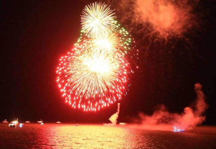 Durante el desfile de embarcaciones, luces multicolores iluminaron el cielo de Chetumal. (Redacción/SIPSE)