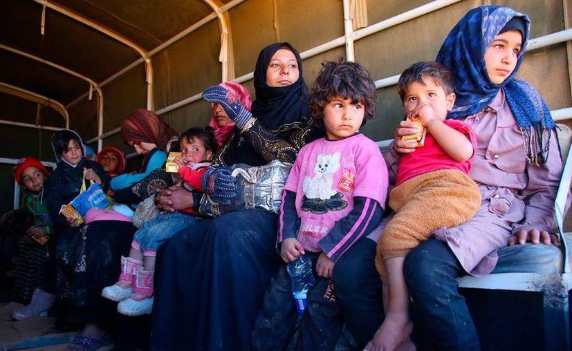 Activistas opositores sirios aseguraron que más de 70 personas murieron en ataques simultáneos del Estado Islámico, donde la guerra ha cobrado miles de víctimas y ha desplazados a miles de personas, como las de la imagen que viajan en un vehículo de la Armada de Jordania. (AP)