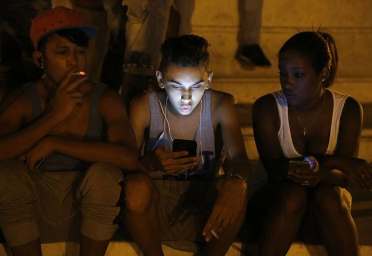 Jóvenes usan sus teléfonos celulares para navegar por Internet utilizando una red wifi protegida de un hotel cinco estrellas en La Habana, Cuba. (Agencias)