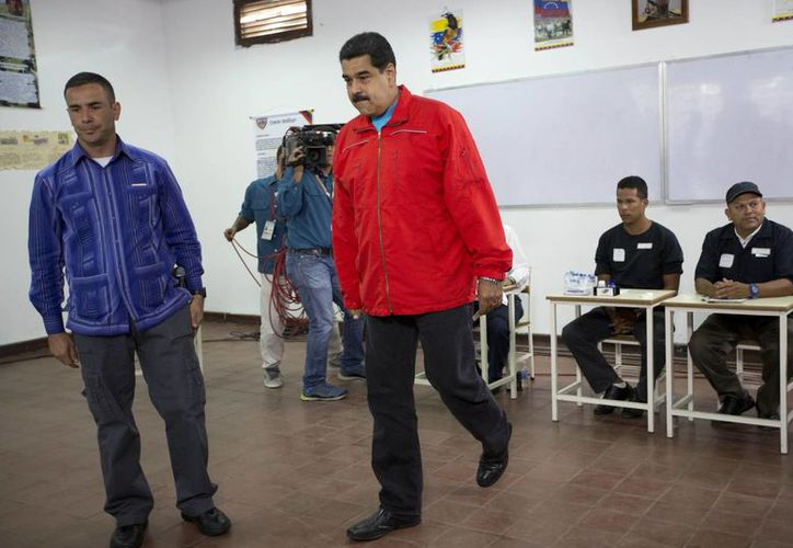 El presidente Nicolás Maduro después de emitir su voto este domingo en Caracas. El mandatario venezolano aceptó la derrota de su partido y afirmó que en su país triunfó la constitución y la democracia. (Imágenes de AP)