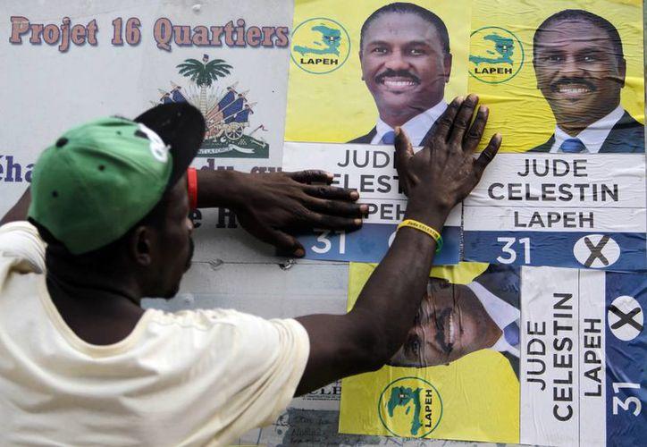 Un hombe pega carteles del candidado presidencial Jude Celestin, en Puerto Príncipe, el 18 de noviembre del 2016. Los haitianos tratarán una vez más de elegir un presidente el 20 de noviembre. (AP/Ricardo Arduengo)