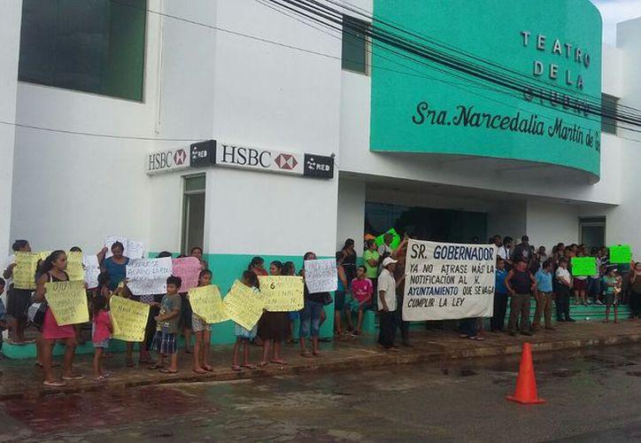 Con pancartas y algunas mantas, hombres, mujeres y niños esperaron al mandatario estatal en la sede del informe del alcalde. (Alejandro Poot/SIPSE)
