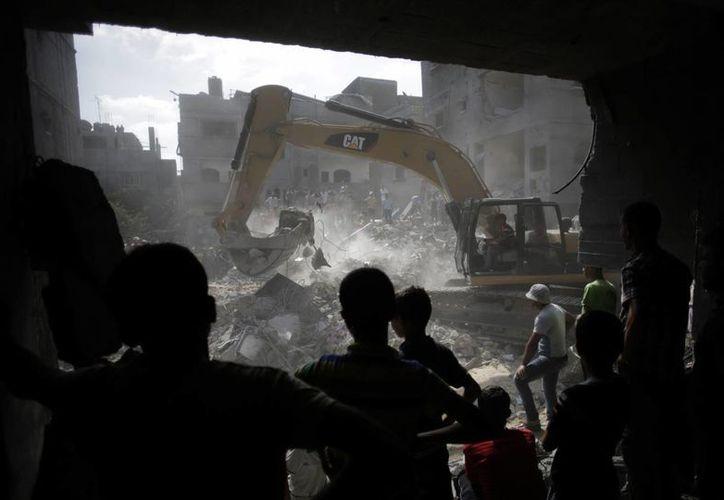 Palestinos se reúnen alrededor de los escombros de una casa destruida tras los ataques israelíes en el campamento de refugiados de Rafah, al sur de la Franja de Gaza. (Agencias)